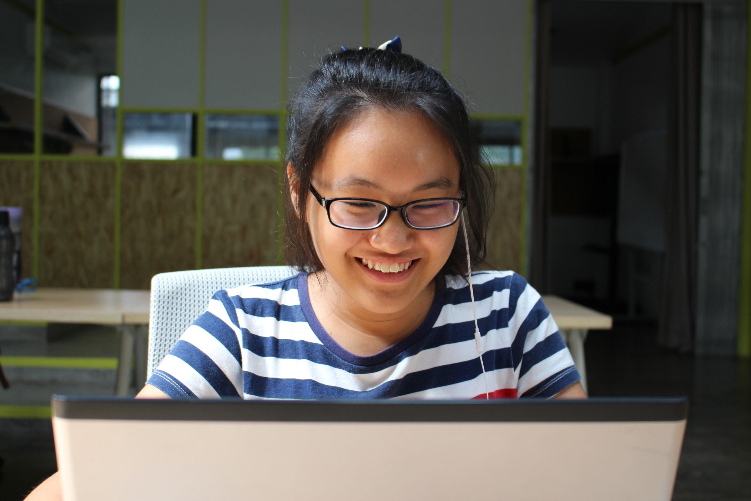 intern smiling at her computer at work